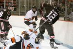 Mike Ambrosia falls as he fights for the puck with Josh McArdle